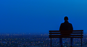 man on park bench looking over night city